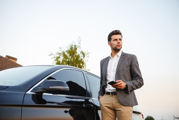 Confident young businessman in suit standing at his car Premium Photo