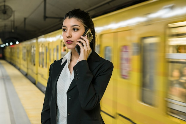 Confident young businessman talking on mobile phone standing near the moving yellow train Free Photo