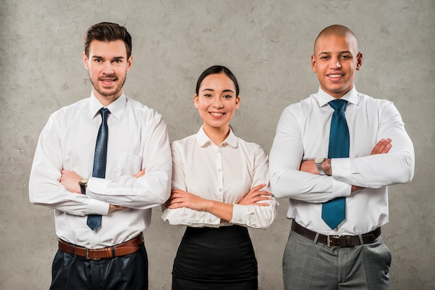 Confident young businessmen and businesswoman with their arms crossed looking to camera Free Photo