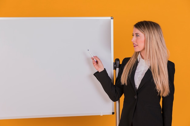 Confident young businesswoman giving presentation on whiteboard against an orange backdrop Free Photo