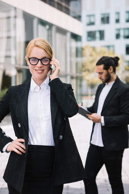 Confident young businesswoman talking on cell phone with her colleague working at background Free Photo
