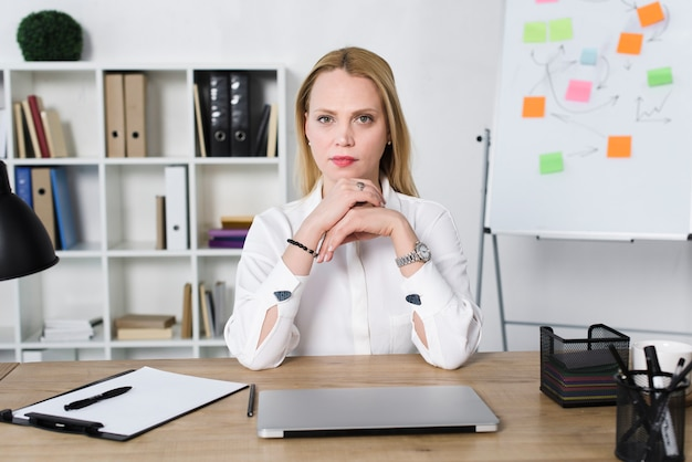 Confident young businesswoman with laptop on table in the office Free Photo