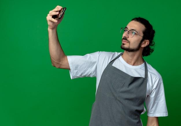 コピースペースで緑の背景に分離されたselfieを取っている制服と眼鏡を身に着けている自信を持って若い白人男性理髪店 無料写真