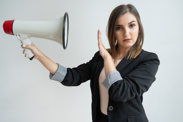 Confident young caucasian woman directing megaphone at herself Free Photo