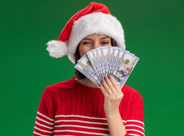 Confident young girl wearing santa hat holding money  from behind it winking isolated on green wall Free Photo