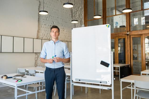 Уверенный молодой красивый улыбающийся человек, стоящий на пустой белой доске с маркером, Бесплатные Фотографии