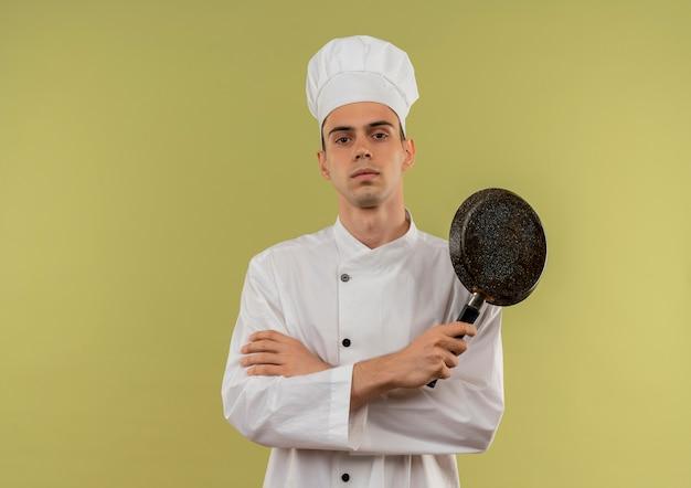 Fiducioso giovane cuoco maschio indossa uniforme chef incrocio mani che tengono padella sulla parete verde isolata con lo spazio della copia Foto Gratuite