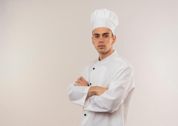 Fiducioso giovane maschio cuoco indossa uniforme chef incrocio le mani sul muro bianco isolato con copia spazio Foto Gratuite
