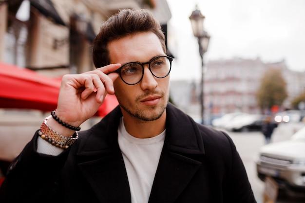 ヨーロッパの都市で屋外に立っている間よそ見フルスーツで自信を持って若い男。アイウェアを着用しています。スタイリッシュなヘアスタイラー。 無料写真