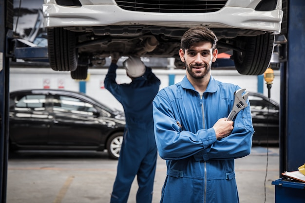 Confident young mechanic standing with his arms crossed while workmate working. Premium Photo