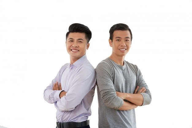 Confident young people standing shouder to shoulder with arms folded against white background Free Photo