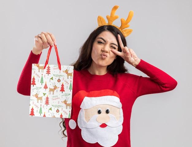 トナカイの角のヘッドバンドとサンタクロースのセーターを身に着けている自信を持って若いかわいい女の子は、目のまばたきの近くにvサインのシンボルを表示してクリスマスギフトバッグを保持しています 無料写真