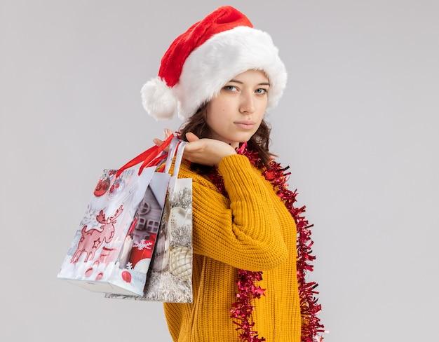 サンタの帽子と首に花輪を持つ自信を持って若いスラブの女の子は肩に紙のギフトバッグを保持します 無料写真