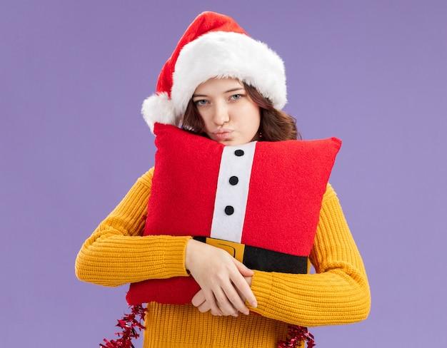 サンタの帽子と首の周りに花輪を持つ自信を持って若いスラブの女の子は、コピースペースで紫色の背景に分離されたカメラを見て装飾された枕を抱擁します 無料写真
