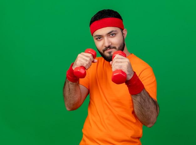 Fiducioso giovane sportivo da indossare fascia e braccialetto in piedi in posa di combattimento Foto Gratuite