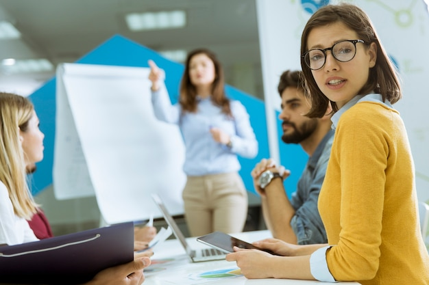 Confident young team leader giving a presentation to a group of young colleagues as they sit grouped by the flip chart in the office Premium Photo