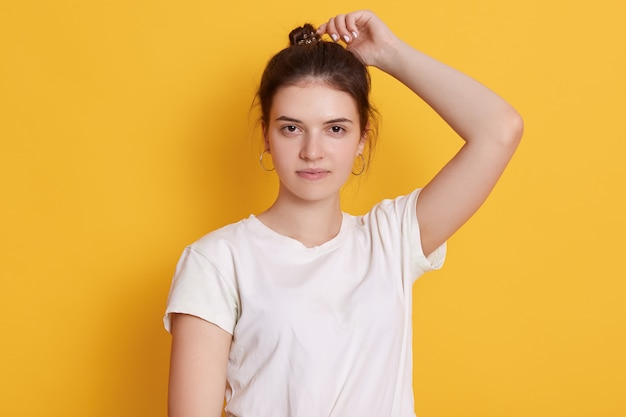 Confident young woman being photographed against yellow wall Free Photo