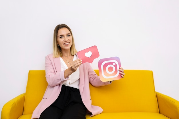 Confident young woman holding instagram and like icon 23 2147847506