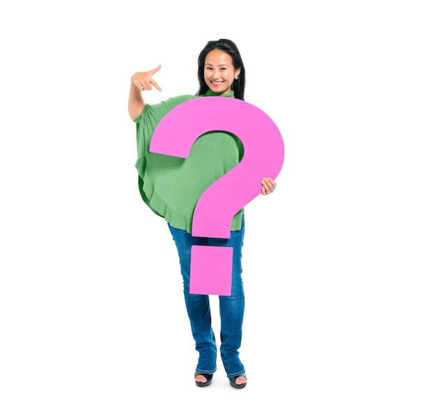 Confident young woman holding and pointing question mark Free Photo
