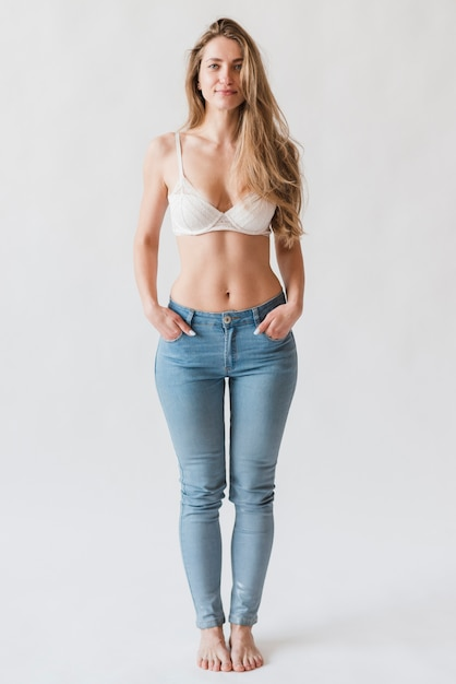 Confident young woman posing in bra and denim Free Photo