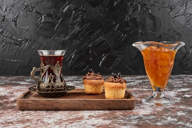 Конфитюр, кексы и стакан чая на деревянной доске. Бесплатные Фотографии