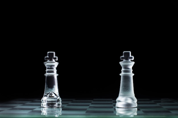 Confrontation - two wooden chess king standing against each other on a chessboard. Free Photo