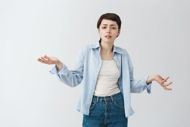 Смущенная и разочарованная девушка пожимает плечами и выглядит сложным, не может понять Бесплатные Фотографии