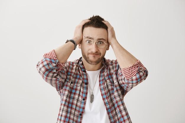 Смущенный и напряженный молодой парень в очках позирует Бесплатные Фотографии