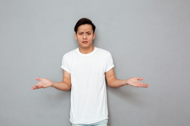 Confused asian man standing over grey wall Free Photo