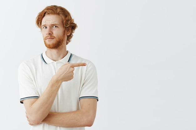 Ragazzo confuso con la barba rossa in posa contro il muro bianco Foto Gratuite
