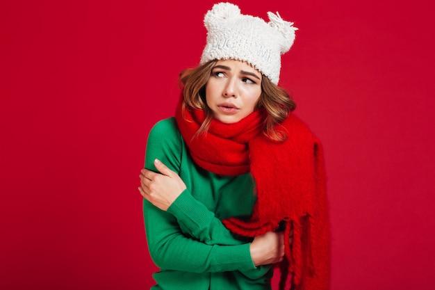 Donna confusa del brunette in maglione, cappello divertente e sciarpa Foto Gratuite