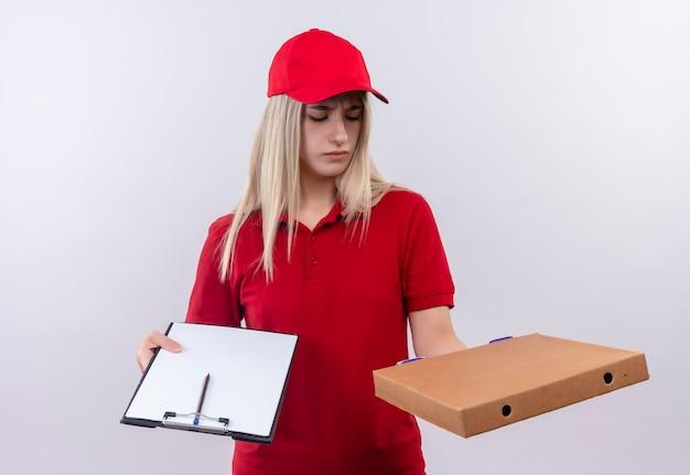 孤立した白い壁に手にピザボックスを探しているクリップボードを保持している赤いtシャツとキャップを身に着けている混乱した配達若い女性 無料写真