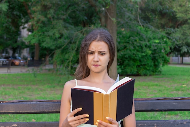 Confused and displeased girl is reading a book on the bench in the park Premium Photo