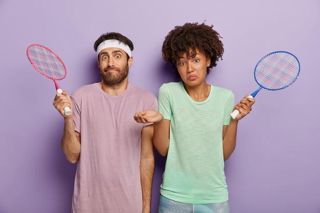 混乱している多様な女性と男性のテニスプレーヤーはラケットを持って立っており、無知な表情をしており、紫色の壁に隔離されたtシャツを着たコートを見つけることができません。好きなゲームのコンセプト 無料写真
