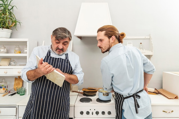 Confused father and son looking in a cookery book Free Photo