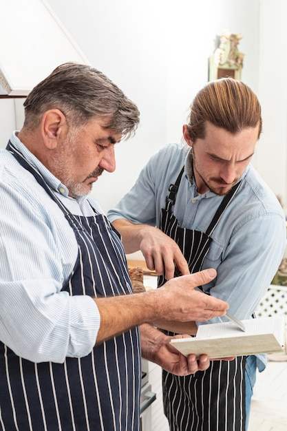 Confused father and son looking on a recipe Free Photo