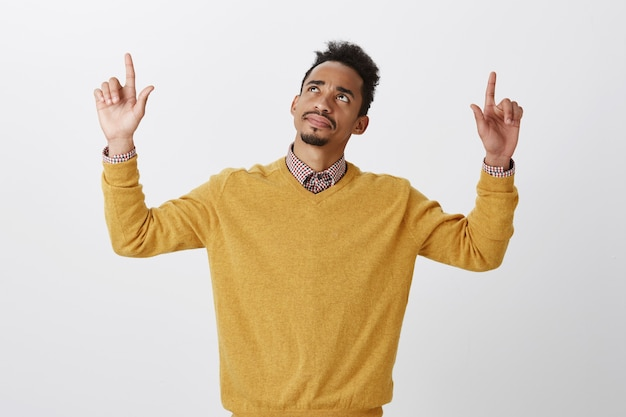 혼란스러워하는 남자, 위층에서 뭔가를 인식하는 데 문제가 있습니다. 아프로 헤어 스타일을 가진 아름다운 어두운 피부의 남성 모델에 의문을 제기하고, 손을 들고, 의심과 의심으로 가리키고 올려다 보았습니다. 무료 사진