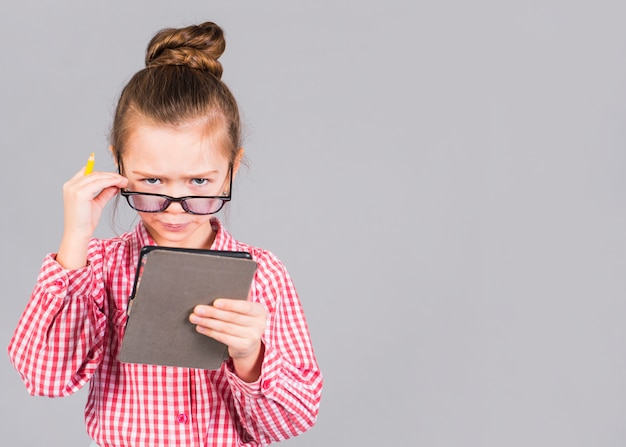 Confused little girl in glasses using tablet Free Photo