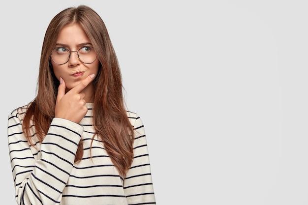 Смущенная милая девушка-подросток держит подбородок, задумчиво смотрит в сторону, у нее темные волосы, носит полосатый свитер, изолирована на белой стене Бесплатные Фотографии