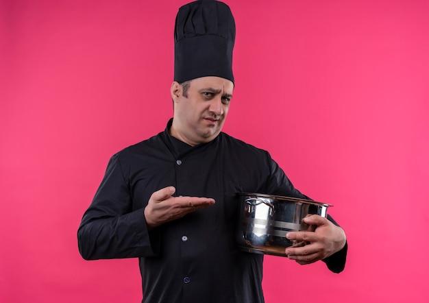 コピースペースと孤立したピンクの壁に彼の手で鍋を示すシェフの制服を着た混乱した中年男性料理人 無料写真