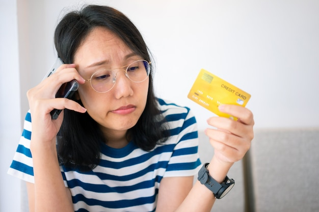 Confused portrait of young woman holding credit cards having problem online payment Premium Photo