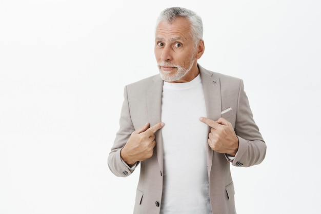 Confused and shocked senior man pointing at himself puzzled Free Photo