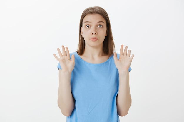 Confused and startled woman raising hands up in surrender, unwilling to be involved Free Photo