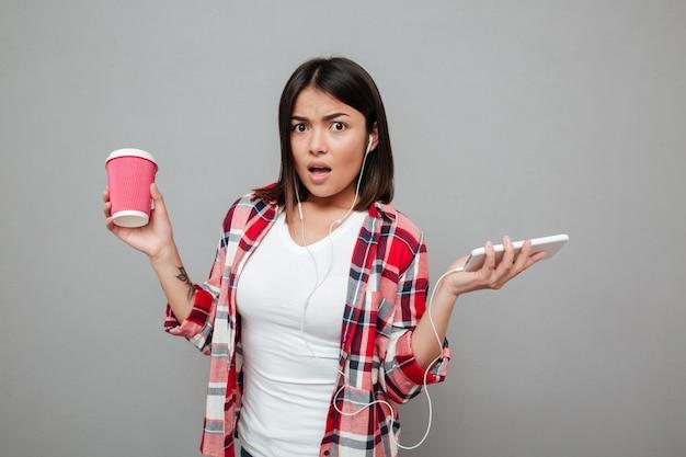 一杯のコーヒーを押しながら音楽を聴いて混乱している女性。 無料写真