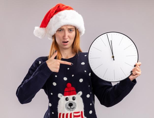 Confusa giovane bella ragazza che indossa il cappello di natale che tiene e punti all'orologio di parete isolato su priorità bassa bianca Foto Gratuite