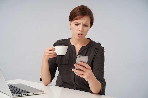 彼女の携帯電話の画面を見ながら眉を眉をひそめ、白でポーズをとっている間お茶を持って、短い流行のヘアカットで混乱した若い茶色の髪の女性 無料写真