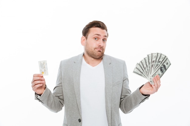 Confused young businessman holding credit card and money. Free Photo