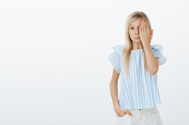 恥ずかしい何かを見てぎこちない感じで混乱している若い女の子。片方の目を手のひらで覆うかわいい髪のかわいいかわいい娘 無料写真