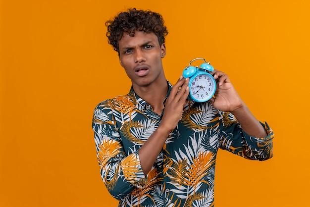 Смущенный молодой красивый темнокожий мужчина с вьющимися волосами в рубашке с принтом листьев держит синий будильник и показывает время Бесплатные Фотографии