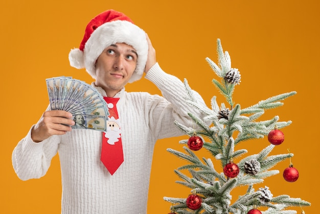 Confused young handsome guy wearing christmas hat and santa claus tie standing near decorated christmas tree holding money keeping hand on head looking at side isolated on orange wall Free Photo